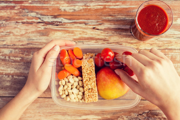 close up of hands with vegetarian food in box Stock photo © dolgachov