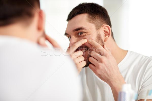 smiling man squeezing pimple at bathroom mirror Stock photo © dolgachov