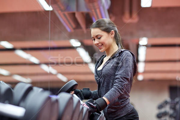Stock photo: young smiling woman choosing dumbbells in gym