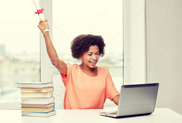 happy african woman with laptop, books and diploma Stock photo © dolgachov