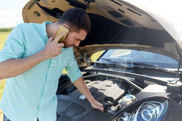 man with broken car calling on smartphone Stock photo © dolgachov