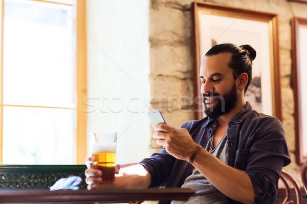 Człowiek smartphone pitnej piwa bar publikacji Zdjęcia stock © dolgachov