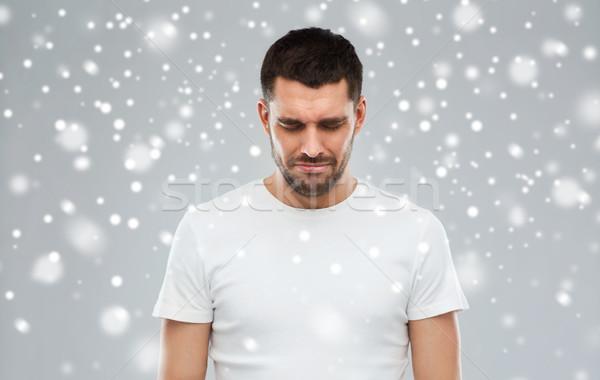 unhappy young man over snow background Stock photo © dolgachov