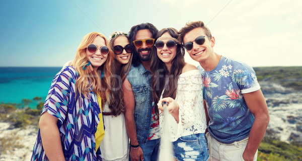happy hippie friends with selfie stick on beach Stock photo © dolgachov