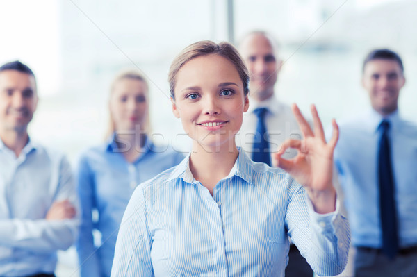 smiling businesswoman showing ok sign in office Stock photo © dolgachov