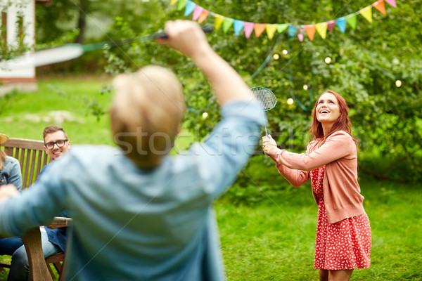 happy friends playing badminton at summer garden Stock photo © dolgachov