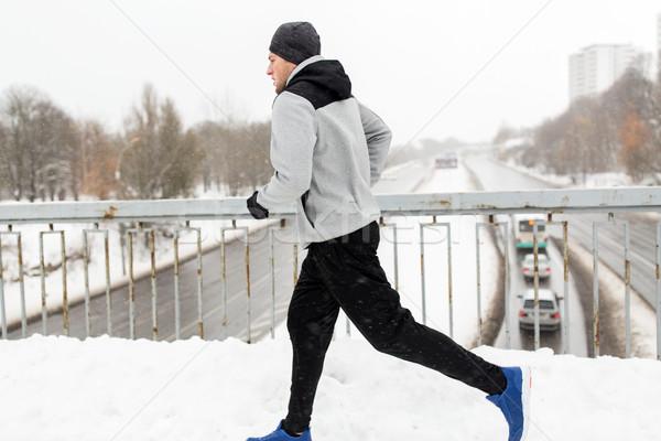 man running along snow covered winter bridge road Stock photo © dolgachov