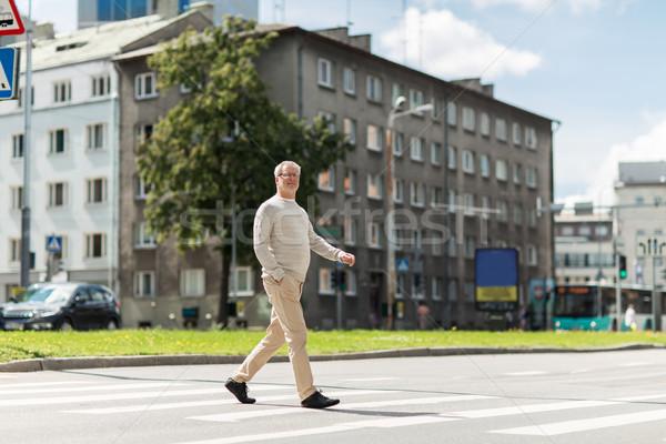 senior man walking along city crosswalk Stock photo © dolgachov