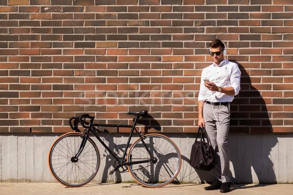 man with headphones, smartphone and bicycle Stock photo © dolgachov