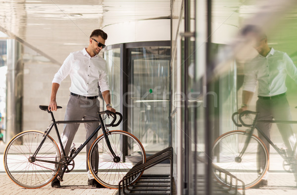 young man parking his bicycle on city street Stock photo © dolgachov