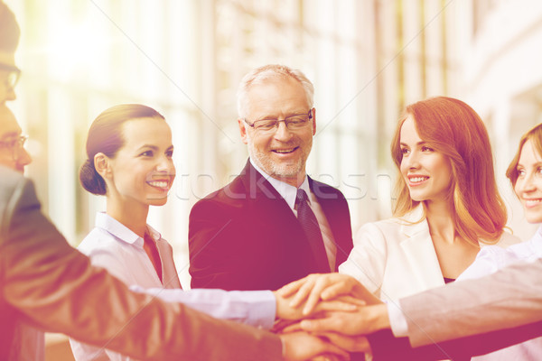 business people putting hands on top in office Stock photo © dolgachov