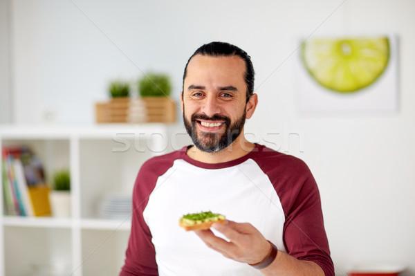 Uomo mangiare avocado panini home cucina Foto d'archivio © dolgachov