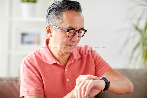 asian man checking time on wristwatch at home Stock photo © dolgachov