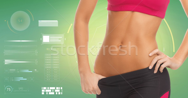 close up of sporty woman abdomen over green Stock photo © dolgachov