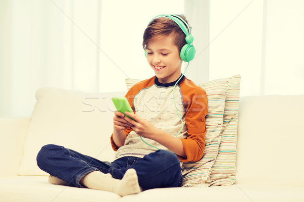 happy boy with smartphone and headphones at home Stock photo © dolgachov