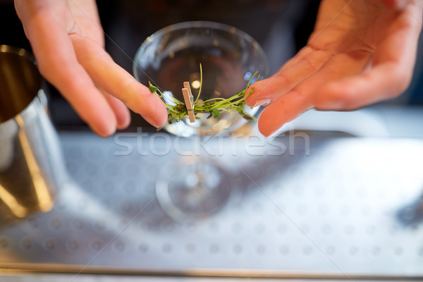 bartender decorating glass of cocktail at bar Stock photo © dolgachov