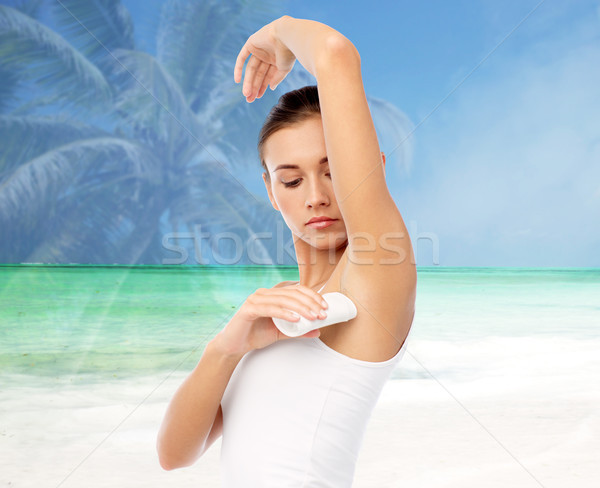 woman with antiperspirant deodorant over beach Stock photo © dolgachov