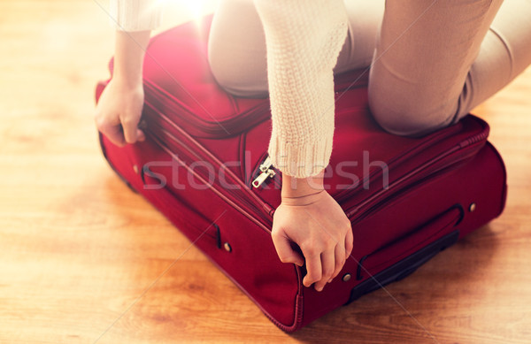 Stock photo: close up of woman packing travel bag for vacation