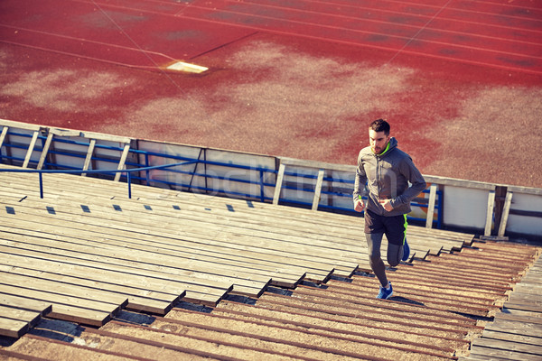 happy young man running upstairs on stadium Stock photo © dolgachov
