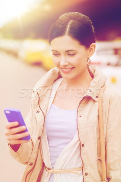 Mosolygó nő okostelefon taxi város utazás üzleti út Stock fotó © dolgachov
