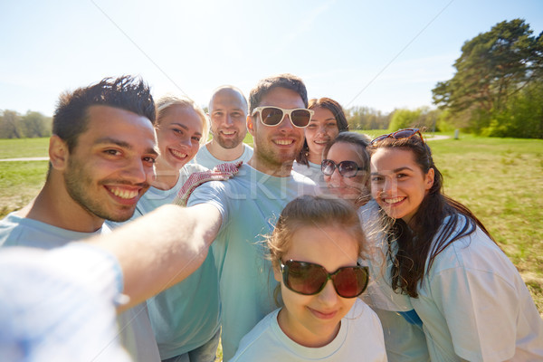 group of volunteers taking selfie by smartphone Stock photo © dolgachov