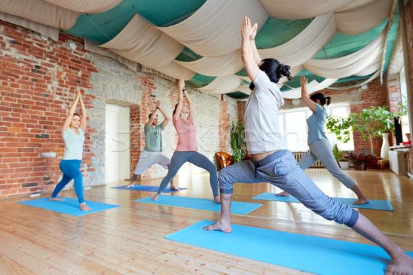 Groupe de gens yoga guerrier posent studio fitness Photo stock © dolgachov