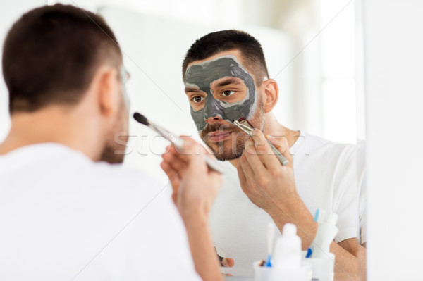 Stock photo: young man applying clay mask to face at bathroom