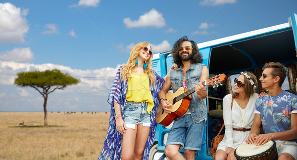 hippie friends playing music at minivan in africa Stock photo © dolgachov
