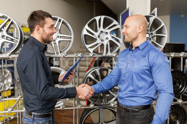 auto business owner and wheel rims at car service Stock photo © dolgachov