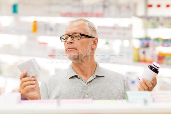 senior male customer choosing drugs at pharmacy Stock photo © dolgachov