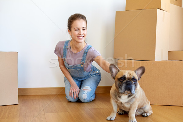 happy woman with dog and boxes moving to new home Stock photo © dolgachov