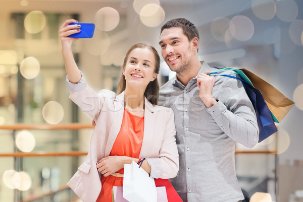 happy couple with smartphone taking selfie in mall Stock photo © dolgachov