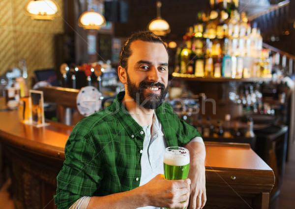 happy man drinking green beer at bar or pub Stock photo © dolgachov