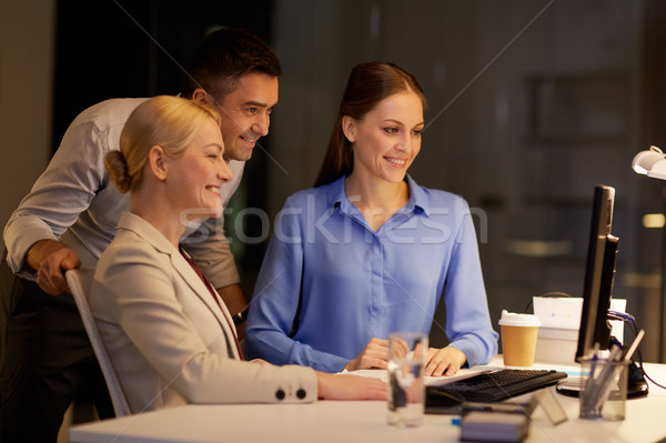 business team with computer working late at office Stock photo © dolgachov