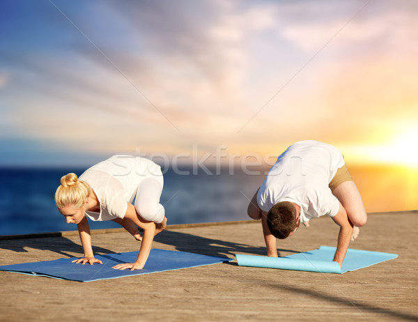 couple doing yoga crow pose outdoors Stock photo © dolgachov