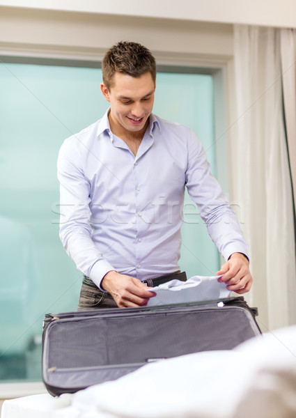 businessman packing things in suitcase Stock photo © dolgachov