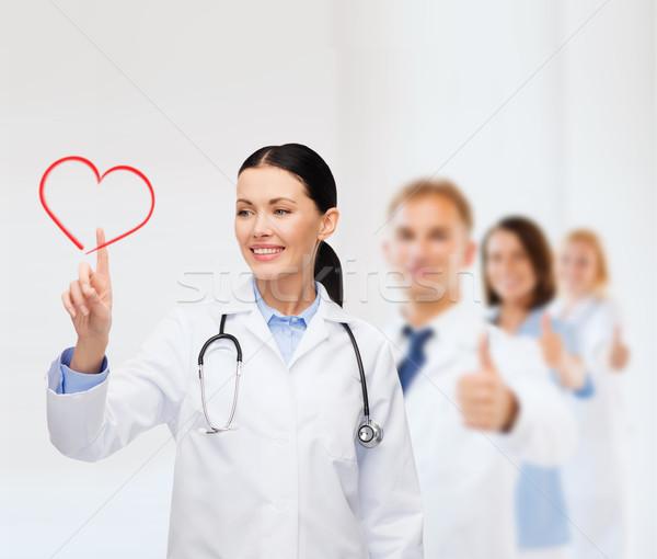 smiling female doctor pointing to heart Stock photo © dolgachov