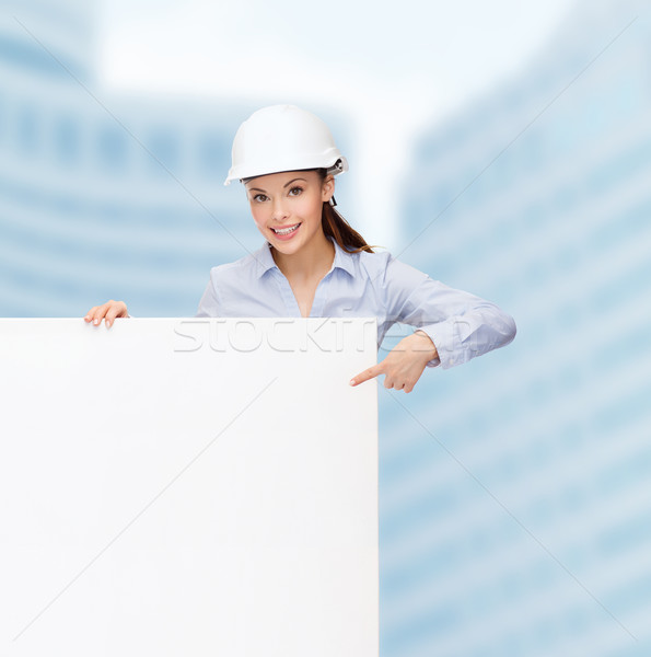 businesswoman in helmet pointing finger to board Stock photo © dolgachov