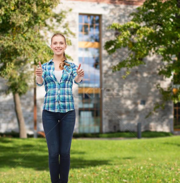 Fiatal nő lezser ruházat mutat remek boldogság Stock fotó © dolgachov