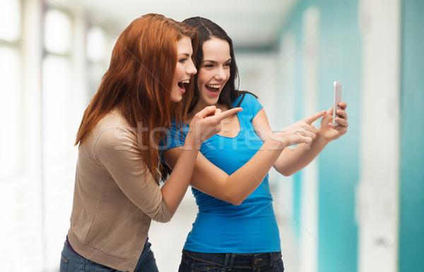 Dos sonriendo adolescentes tecnología amistad Foto stock © dolgachov