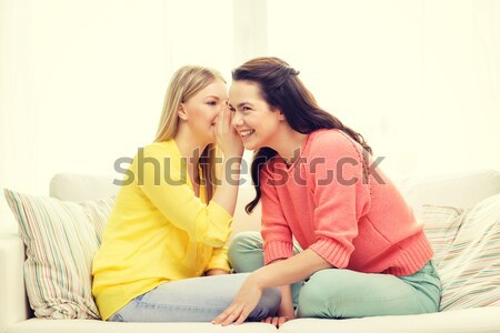 one girl telling another secret Stock photo © dolgachov