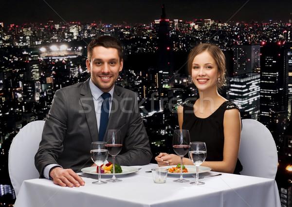 smiling couple eating main course at restaurant Stock photo © dolgachov