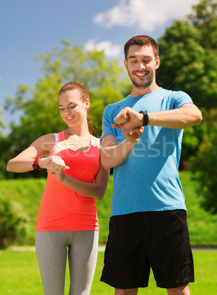 smiling people with heart rate watches outdoors Stock photo © dolgachov