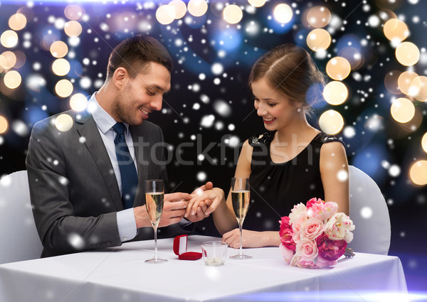 smiling couple with red gift box at restaurant Stock photo © dolgachov