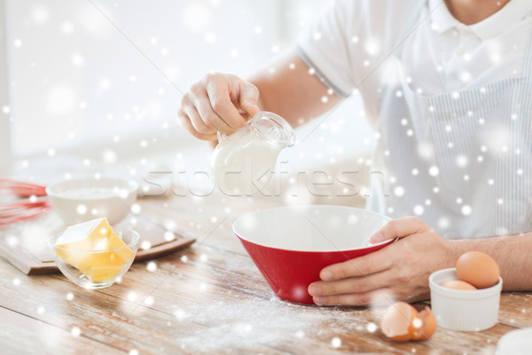 close up of man pouring milk to bowl Stock photo © dolgachov
