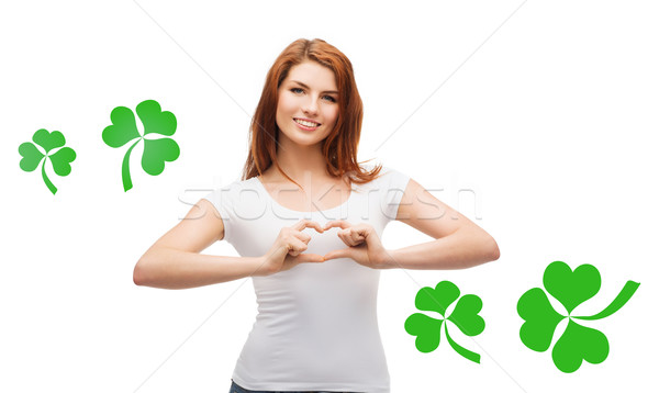 smiling girl showing heart gesture with shamrock Stock photo © dolgachov