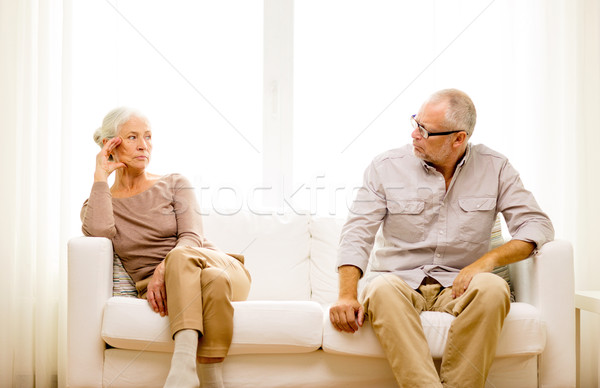 senior couple sitting on sofa at home Stock photo © dolgachov