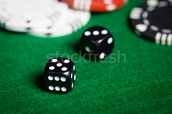 close up of black dices on green casino table Stock photo © dolgachov