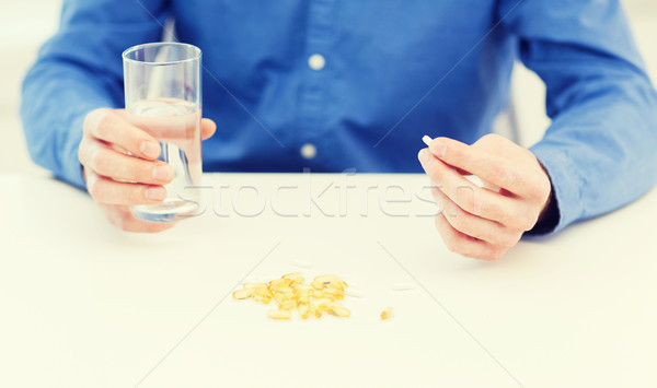 male hand holding pill and glass of water Stock photo © dolgachov