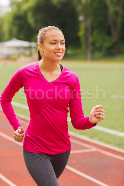 smiling young woman running on track outdoors Stock photo © dolgachov